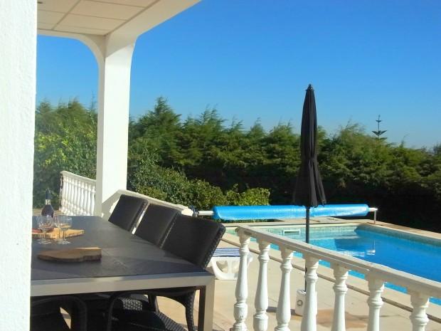 Via de schuifpui op het overdekte terras en het zonneterras bij het zwembad